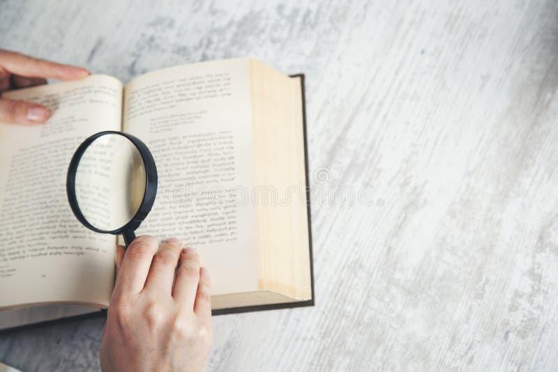 Βιβλίο χεριών γυναικών και πιό magnifier στοκ φωτογραφίες