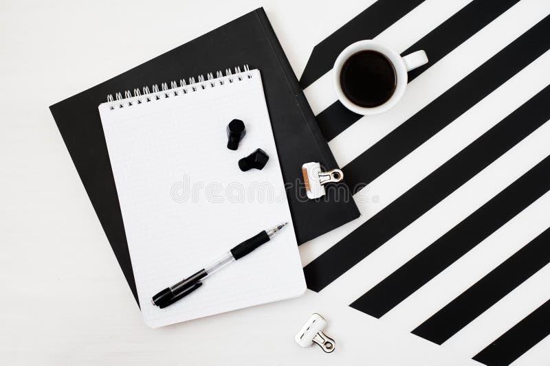 Βιβλίο χώρου εργασίας Minimalistic, σημειωματάριο, μολύβι, φλιτζάνι του καφέ, ακουστικά στο ριγωτό γραπτό υπόβαθρο Επίπεδη άποψη  στοκ φωτογραφίες