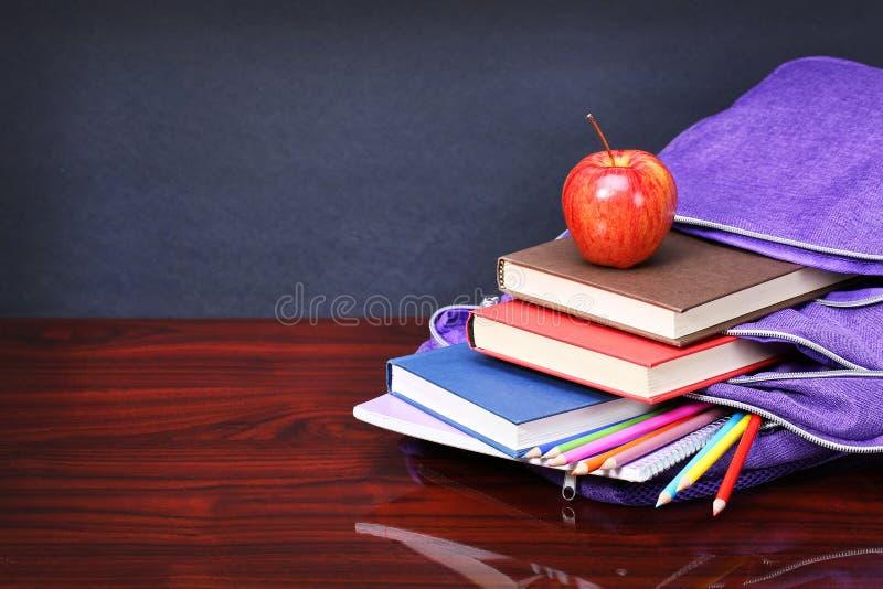 Βιβλία, μήλο, σακίδιο πλάτης και μολύβια στον ξύλινο πίνακα γραφείων στοκ φωτογραφία με δικαίωμα ελεύθερης χρήσης