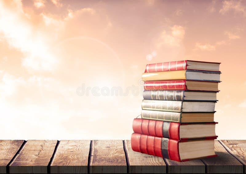 Βιβλία που συσσωρεύονται από τα ηλιόλουστα σύννεφα στοκ φωτογραφίες