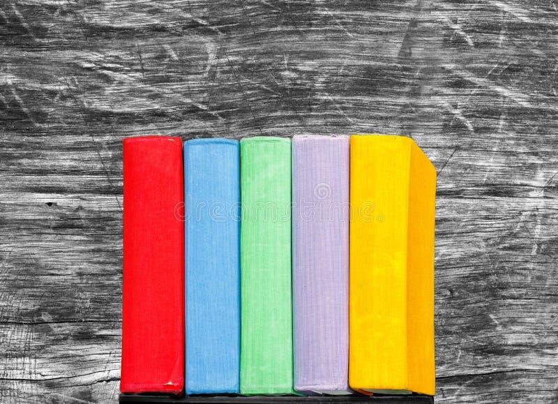 Βιβλία στο παλαιό ξύλινο υπόβαθρο Πολύχρωμα εγχειρίδια στο ράφι στοκ φωτογραφία