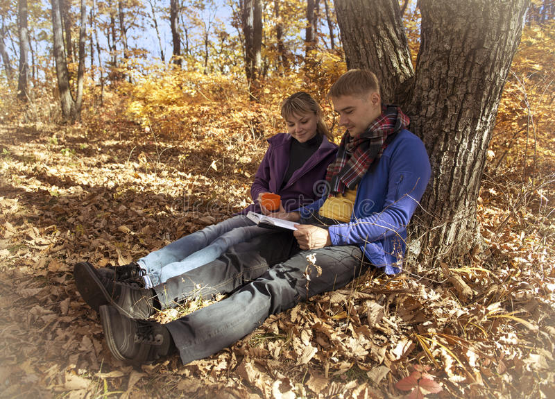 Βιβλίο ανάγνωσης ζεύγους στο δάσος φθινοπώρου στοκ εικόνα