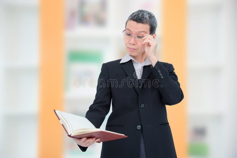 Βιβλίο ανάγνωσης ηλικιωμένων γυναικών που έχει το πρόβλημα με τα μάτια της στοκ φωτογραφίες με δικαίωμα ελεύθερης χρήσης