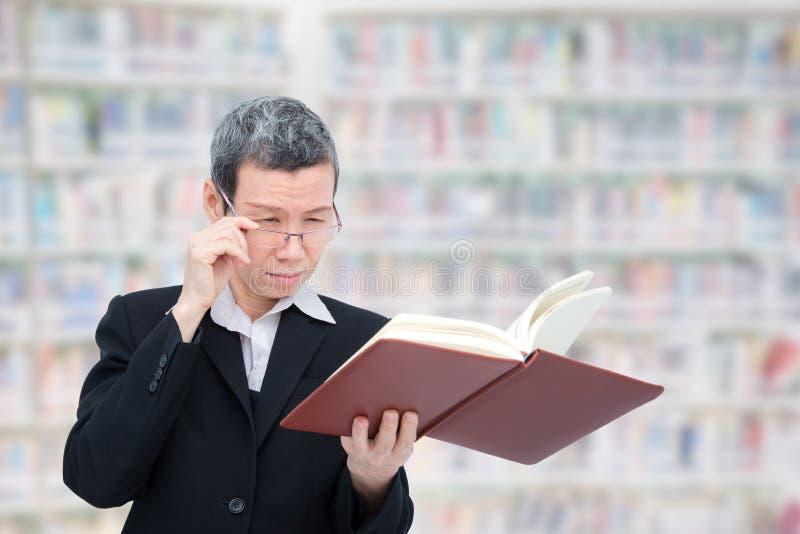 Βιβλίο ανάγνωσης ηλικιωμένων γυναικών που έχει το πρόβλημα με τα μάτια της στοκ εικόνα