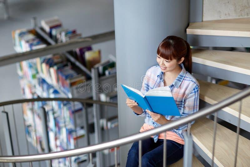 Βιβλίο ανάγνωσης κοριτσιών σπουδαστών γυμνασίου στη βιβλιοθήκη στοκ εικόνες με δικαίωμα ελεύθερης χρήσης