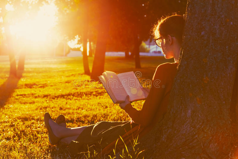 Βιβλίο ανάγνωσης κοριτσιών στο πάρκο στοκ εικόνες