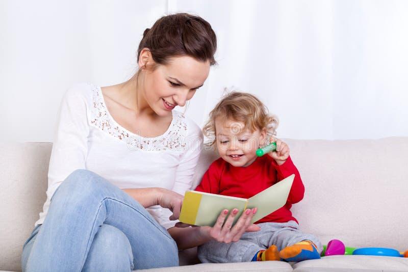 Βιβλίο ανάγνωσης μητέρων με το παιδί στοκ εικόνα