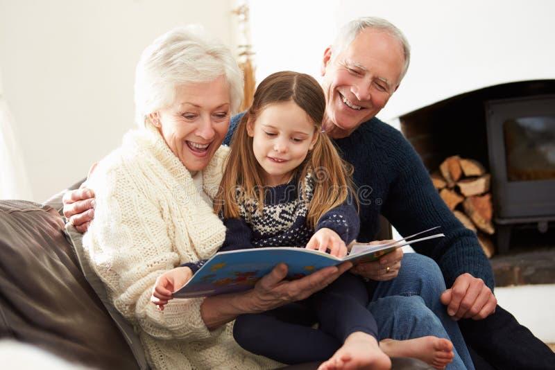 Βιβλίο ανάγνωσης παππούδων και γιαγιάδων και εγγονών στο σπίτι από κοινού στοκ εικόνα με δικαίωμα ελεύθερης χρήσης