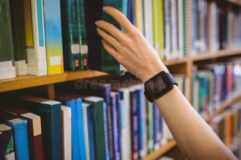 Βιβλίο επιλογής σπουδαστών στη βιβλιοθήκη που φορά το έξυπνο ρολόι στοκ φωτογραφία με δικαίωμα ελεύθερης χρήσης
