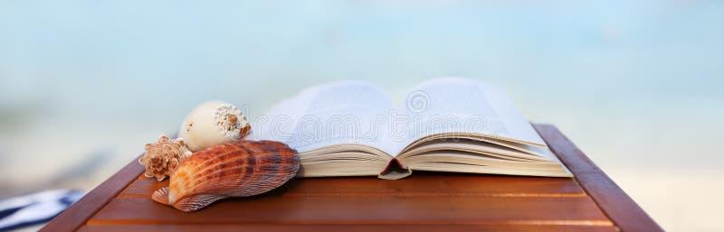 Βιβλίο και κοχύλια στον πίνακα παραλιών στοκ φωτογραφία