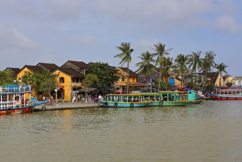 Βιετνάμ, Hoi - τον Ιανουάριο του 2017: Η βάρκα επιπλέει στον ποταμό Bon ενάντια στο σκηνικό των σπιτιών στην προκυμαία στην πόλη  στοκ φωτογραφία