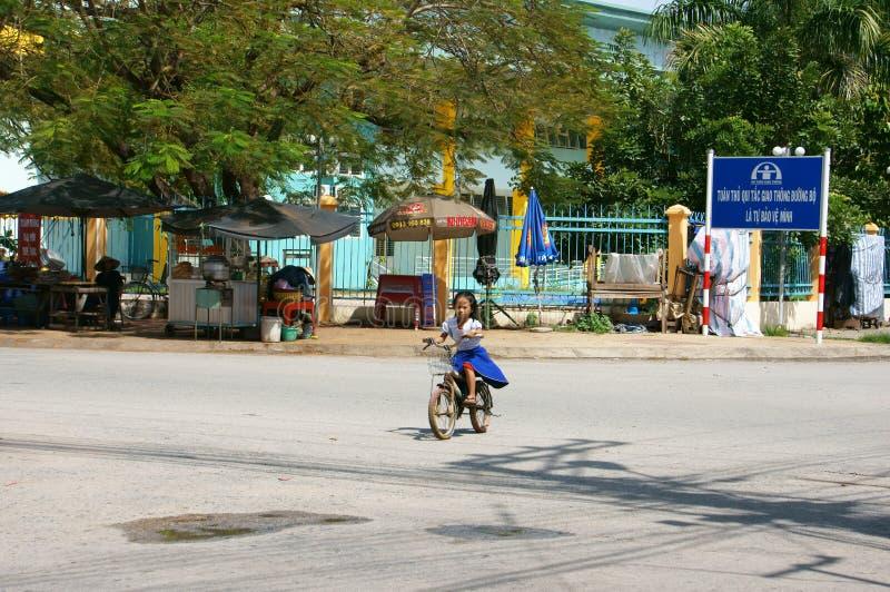 Βιετναμέζικος διαγώνιος δρόμος ποδηλάτων μικρών κοριτσιών οδηγώντας από το σχολείο το μεσημέρι στοκ φωτογραφία με δικαίωμα ελεύθερης χρήσης