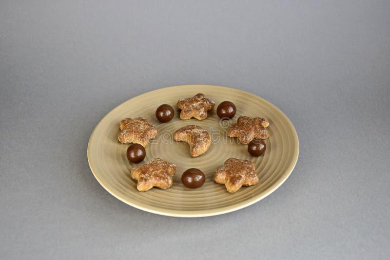 Βιομηχανία ζαχαρωδών προϊόντων, σφαίρες σοκολάτας και μπισκότα σε ένα κεραμικό πιάτο στοκ εικόνα