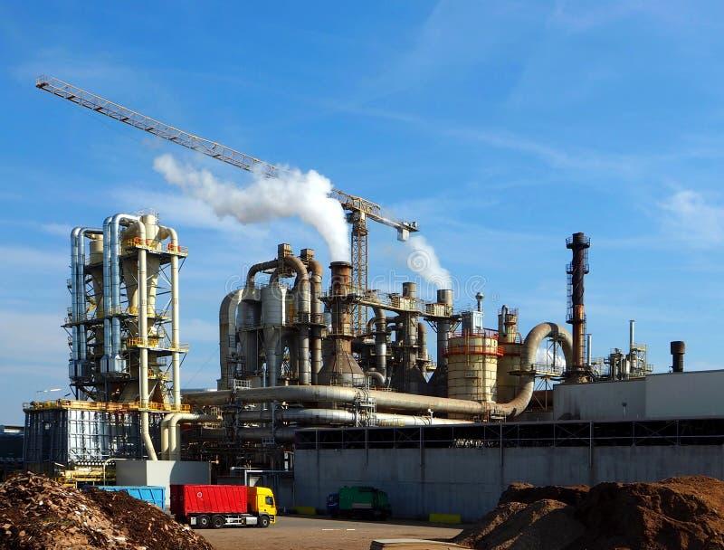 Βιομηχανικές εγκαταστάσεις με τους σωρούς καπνού και έναν γερανό στοκ εικόνες