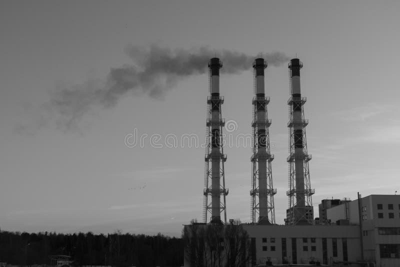 Βιομηχανική άποψη - ο θερμικός σταθμός παραγωγής ηλεκτρικού ρεύματος με τους σωλήνες στην πόλη κοντά στο δάσος από τις καπνοδόχου στοκ φωτογραφία με δικαίωμα ελεύθερης χρήσης