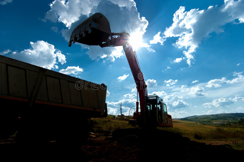 Βιομηχανική γη φόρτωσης εκσκαφέων σε ένα φορτηγό εκφορτωτών στοκ εικόνα με δικαίωμα ελεύθερης χρήσης
