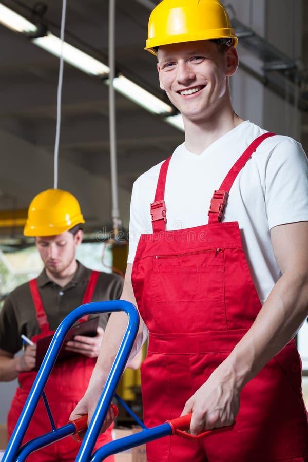 Βιομηχανικοί εργάτες που ωθούν ένα χειρωνακτικό καροτσάκι στοκ εικόνες