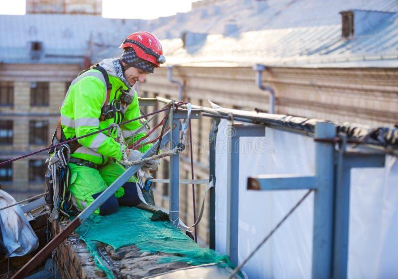 Βιομηχανικός ορειβάτης στη στέγη ενός κτηρίου στοκ φωτογραφία