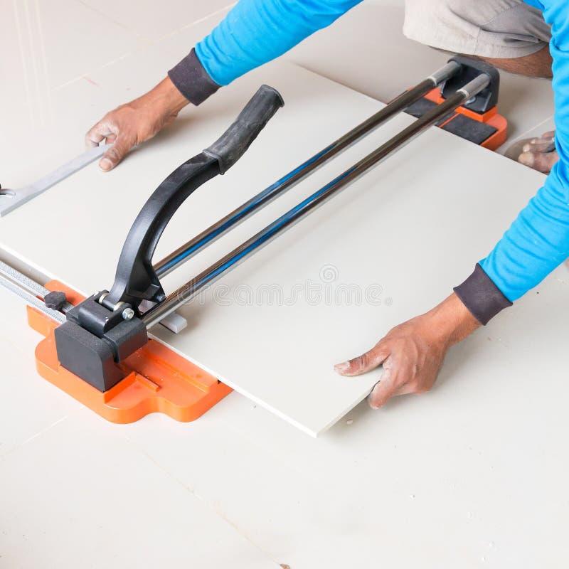 Βιομηχανικός tiler εργαζόμενος οικοδόμων που εργάζεται με τον τέμνοντα εξοπλισμό κεραμιδιών πατωμάτων στοκ φωτογραφίες