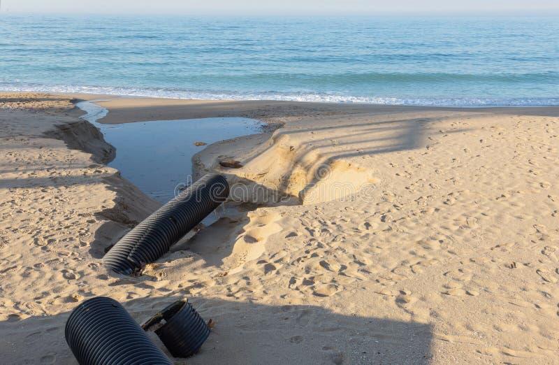 Βιομηχανικό απόβλητο ύδωρ, τα υγρά βιομηχανικά απόβλητα απαλλαγών σωληνώσεων στη θάλασσα σε μια παραλία πόλεων Βρώμικες ροές λυμά στοκ εικόνες