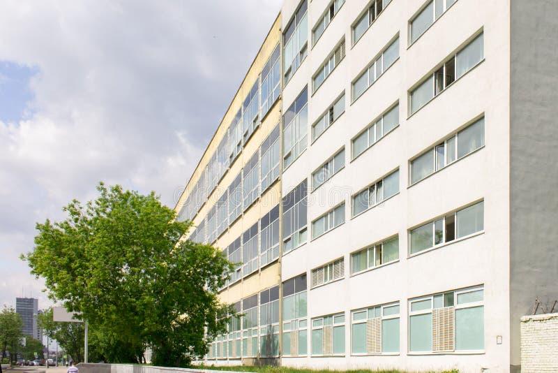 Βιομηχανικό κτήριο με πολλά παράθυρα στην πόλη με ένα πράσινο δέντρο και έναν νεφελώδη ουρανό στο υπόβαθρο στοκ φωτογραφία με δικαίωμα ελεύθερης χρήσης