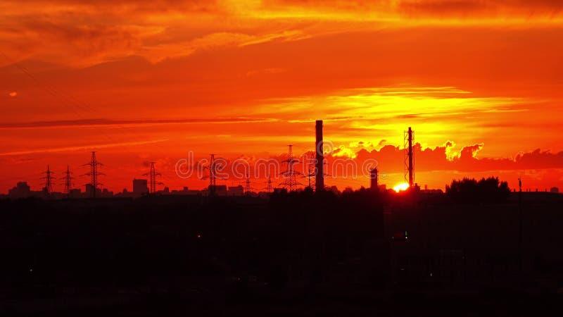Βιομηχανικό πορτοκαλί ηλιοβασίλεμα Ο ήλιος πηγαίνει κάτω πίσω από τους σωλήνες και τους πυλώνες δύναμης απόμακρη πιθανότητα στοκ φωτογραφία με δικαίωμα ελεύθερης χρήσης