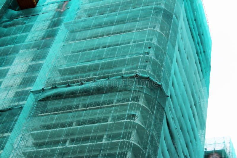 Βιομηχανικό τοπίο εργοτάξιων οικοδομής Ατελές κτήριο που καλύπτεται με το πράσινο πλέγμα στοκ εικόνες