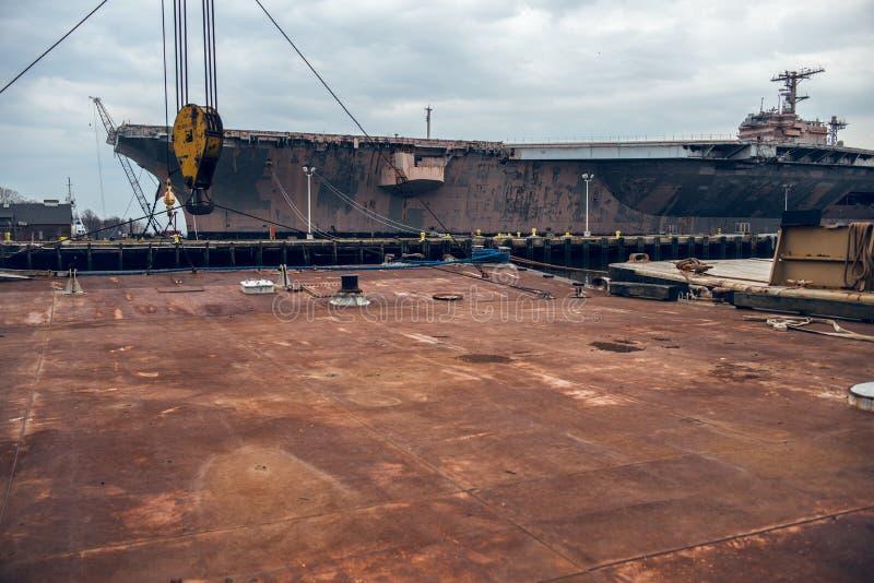 Βιομηχανικό υπόβαθρο της σκουριασμένης πλατφόρμας μετάλλων στο λιμένα αποβαθρών με το θωρηκτό στοκ φωτογραφία