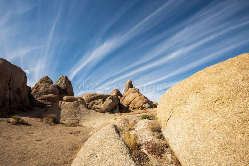 Βιομορφικοί σχηματισμοί πετρωμάτων στην έρημο με σύννεφα που σχηματίζονται στον γαλάζιο ουρανό στοκ εικόνες