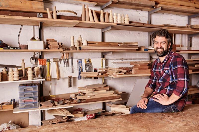 Βιοτέχνης ξυλουργικής στο στούντιο με τα ράφια των ξύλινων κομματιών στοκ φωτογραφία