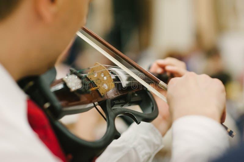 Βιολιστής ατόμων που παίζει το ηλεκτρικό βιολί στοκ φωτογραφία με δικαίωμα ελεύθερης χρήσης