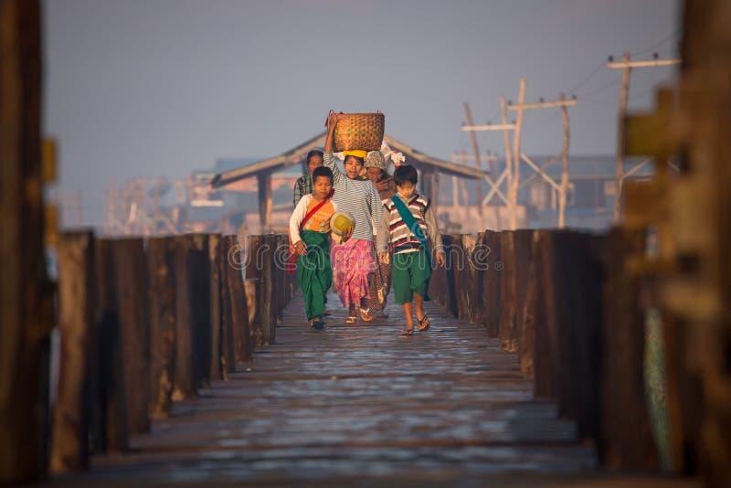 Βιρμανός σπίτι οικογενειακών περιπάτων από την αγορά κατά μήκος της ξύλινης γέφυρας για πεζούς στην ανατολή στοκ φωτογραφία με δικαίωμα ελεύθερης χρήσης