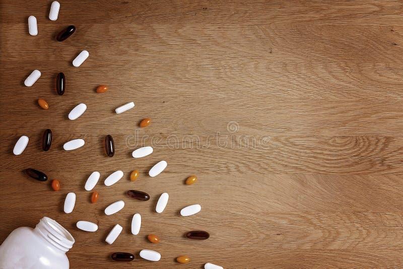 Βιταμίνες, διαιτητικές συμπλήρωμα ή ταμπλέτες pils στον ξύλινο πίνακα Φαρμακείο, ιατρική και έννοια υγείας στοκ εικόνα με δικαίωμα ελεύθερης χρήσης