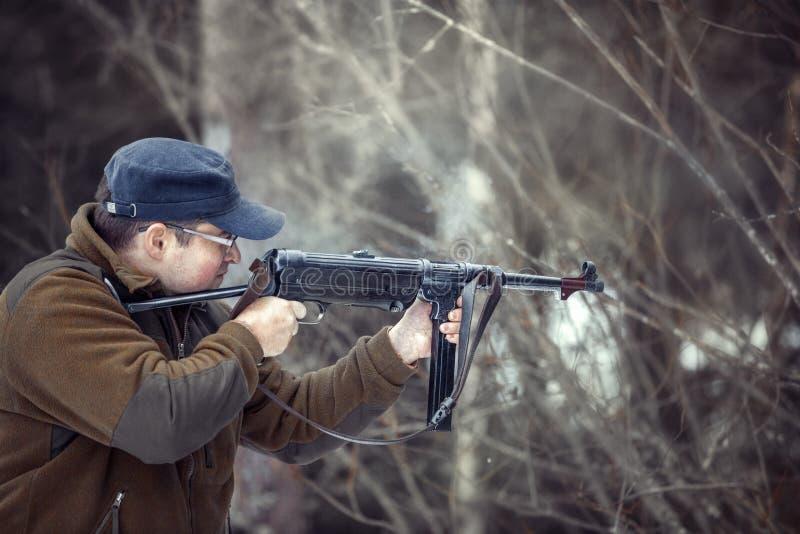 Βλαστοί νεαρών άνδρων από ένα submachine πυροβόλο όπλο στοκ φωτογραφίες με δικαίωμα ελεύθερης χρήσης