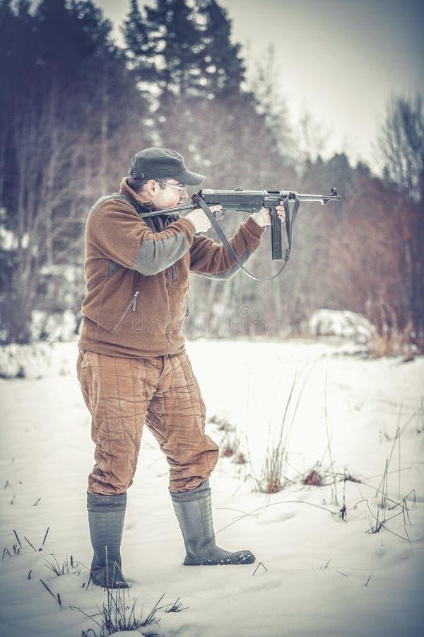 Βλαστοί νεαρών άνδρων από ένα submachine πυροβόλο όπλο στοκ εικόνα με δικαίωμα ελεύθερης χρήσης