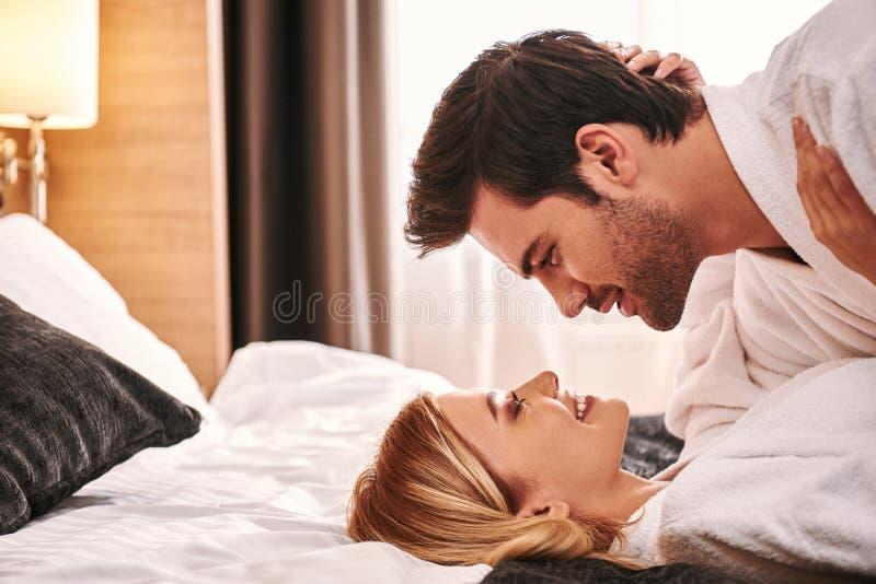 βλαστός αγάπης καρδιών πτώσης βελών Νέο ζεύγος που βρίσκεται μαζί στο κρεβάτι δωματίου ξενοδοχείου στοκ φωτογραφία