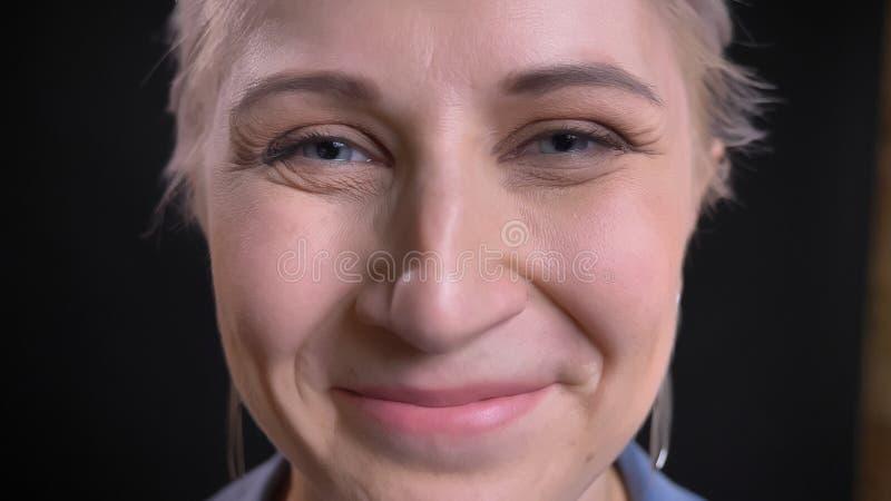 Βλαστός κινηματογραφήσεων σε πρώτο πλάνο του νέου ελκυστικού καυκάσιου θηλυκού με την ξανθή τρίχα και των μπλε ματιών που εξετάζο στοκ φωτογραφίες
