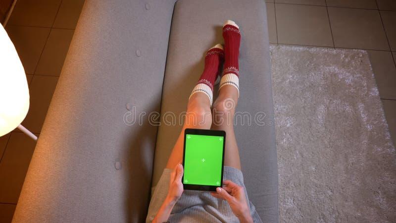 Βλαστός κινηματογραφήσεων σε πρώτο πλάνο του νέου θηλυκού που προσέχει ένα βίντεο στην ταμπλέτα με την πράσινη οθόνη χρώματος Μηρ στοκ εικόνα