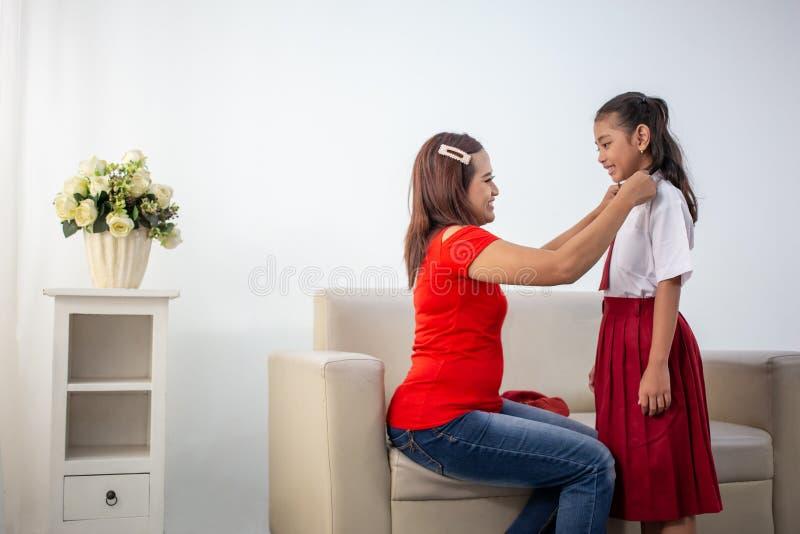 Βοήθεια μητέρων η κόρη της που παίρνει έτοιμη για το σχολείο στοκ εικόνες
