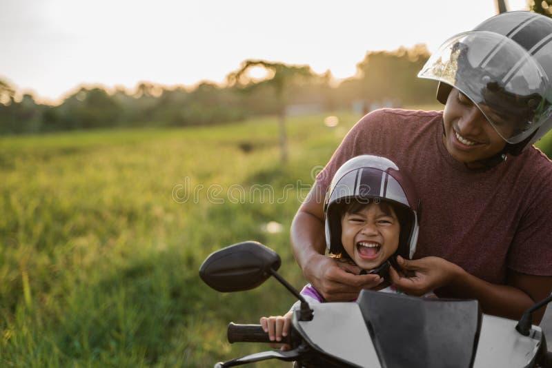 Βοήθεια μπαμπάδων η κόρη της για να στερεώσει το κράνος στοκ εικόνες με δικαίωμα ελεύθερης χρήσης