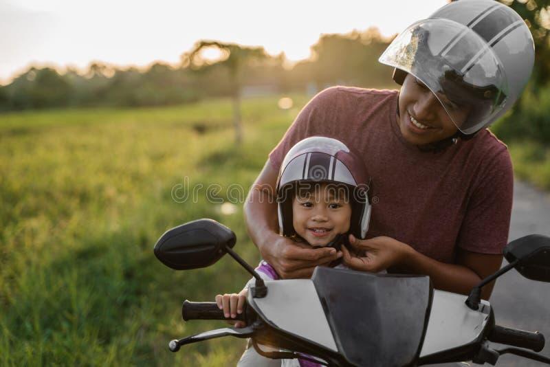 Βοήθεια μπαμπάδων η κόρη της για να στερεώσει το κράνος στοκ φωτογραφίες με δικαίωμα ελεύθερης χρήσης