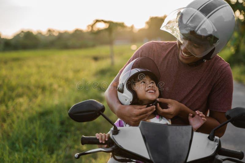 Βοήθεια μπαμπάδων η κόρη της για να στερεώσει το κράνος στοκ φωτογραφία με δικαίωμα ελεύθερης χρήσης