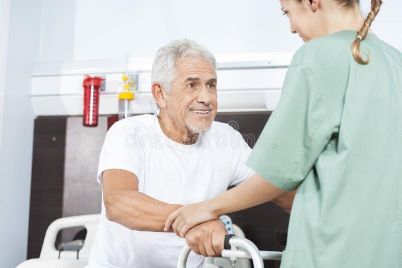Βοήθεια νοσοκόμων που χαμογελά το ανώτερο άτομο σε χρησιμοποίηση του περιπατητή στοκ εικόνες