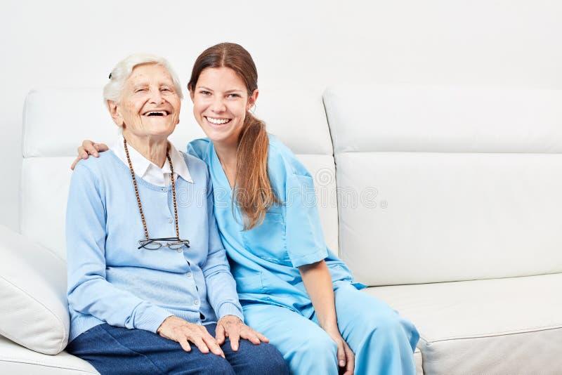 Βοήθεια περιποίησης και γελώντας ευτυχές άτομο τρίτης ηλικίας στοκ φωτογραφίες
