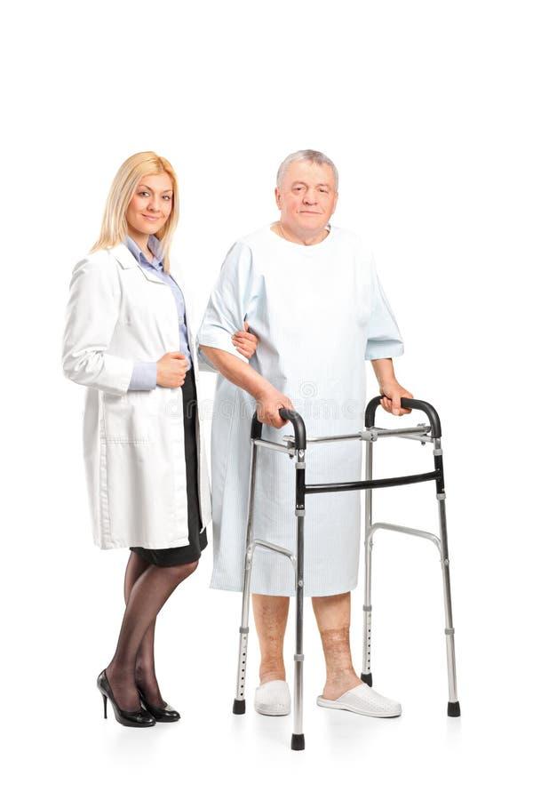 βοήθεια του ασθενή νοσοκόμων για να χρησιμοποιηθεί ο περιπατητής στοκ φωτογραφία