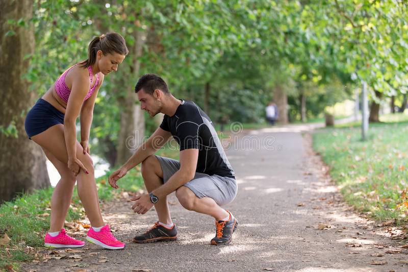 Βοήθειες ανδρών στη γυναίκα με το τραυματισμένο γόνατο στην αθλητική δραστηριότητα στοκ φωτογραφίες με δικαίωμα ελεύθερης χρήσης