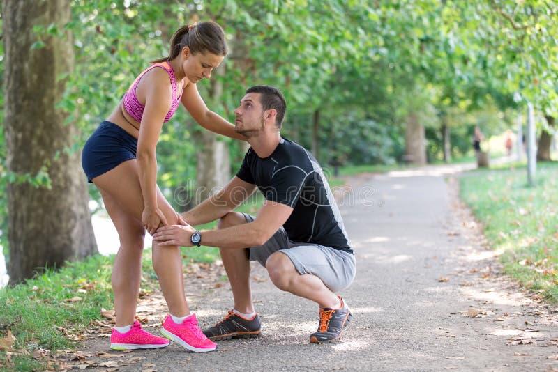 Βοήθειες ανδρών στη γυναίκα με το τραυματισμένο γόνατο στην αθλητική δραστηριότητα στοκ εικόνες με δικαίωμα ελεύθερης χρήσης