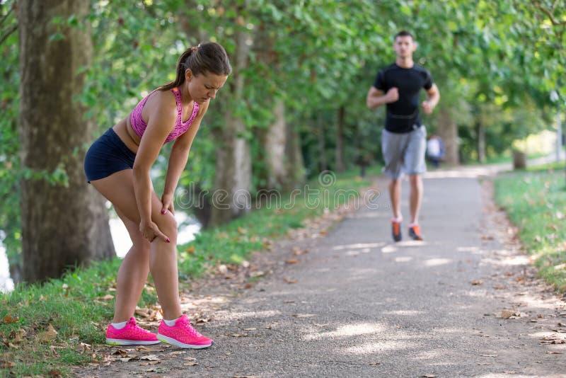 Βοήθειες ανδρών στη γυναίκα με το τραυματισμένο γόνατο στην αθλητική δραστηριότητα στοκ εικόνες