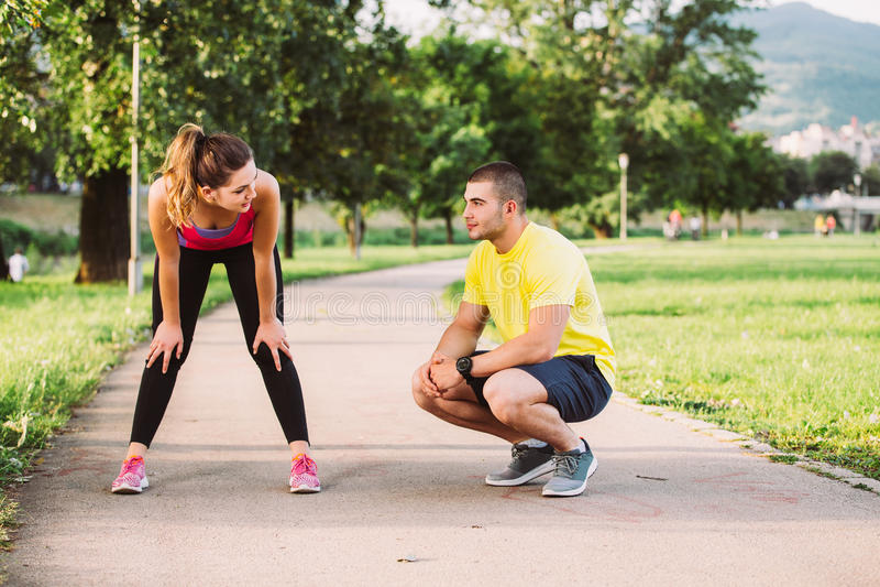Βοήθειες ανδρών στη γυναίκα με το τραυματισμένο γόνατο στην αθλητική δραστηριότητα στοκ εικόνα με δικαίωμα ελεύθερης χρήσης