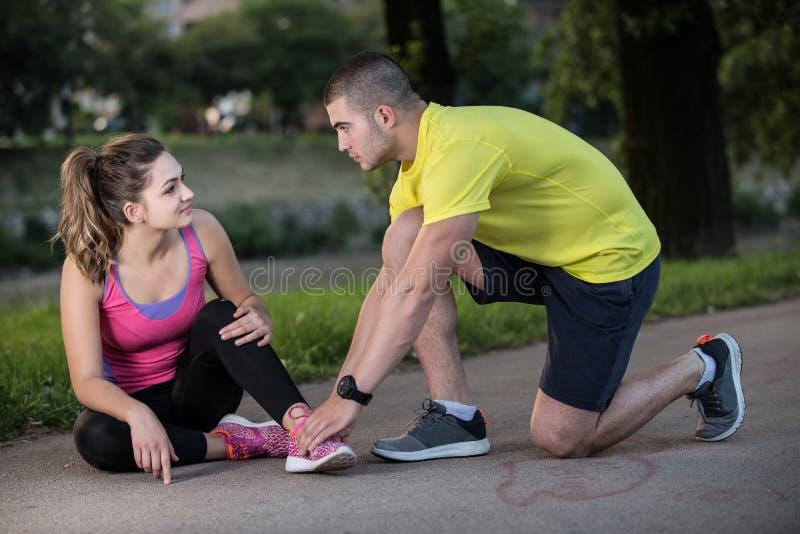 Βοήθειες ανδρών στη γυναίκα με το τραυματισμένο γόνατο στην αθλητική δραστηριότητα στοκ φωτογραφία με δικαίωμα ελεύθερης χρήσης